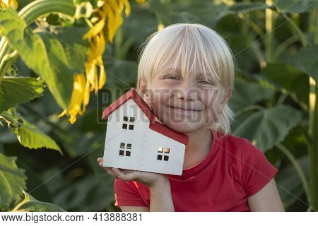 Fair-haired Boy With Small House Is Surrounded By Field Of Sunflowers. Eco-friendly Home. Green Hous