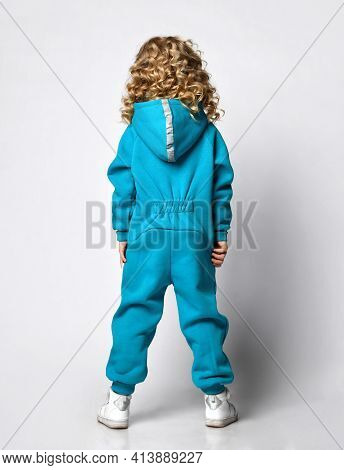 Little Preschooler Or Schoolgirl In A Warm Blue Tracksuit With A Hood And White Sneakers, Stands Wit