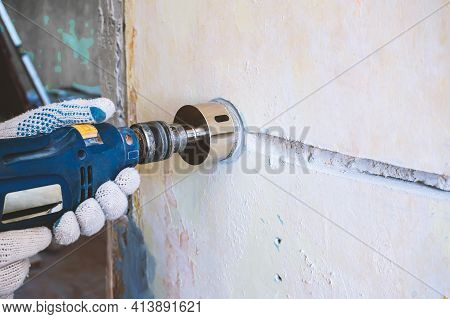 A Worker Drills A Hole For An Electrical Outlet In A Concrete Brick Wall. Repair Of Electrical Wirin