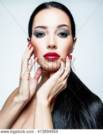 Perfect beauty concept. Fashion portrait of a beautiful female model with professional makeup, isolated on a white background. Young woman with red lipstick and blue eyeshadows.