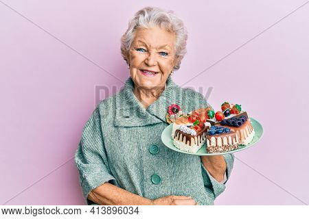 Senior grey-haired woman holding plate with cake slices looking positive and happy standing and smiling with a confident smile showing teeth
