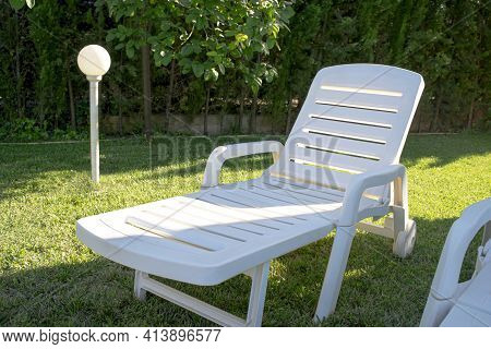 Portable And Reclining Plastic Lounger For Sunbathing And Resting, Placed On The Lawn, With A Lanter
