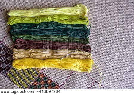 Set Of Multi-colored Cotton Threads And Fragment Of Colorful Cross-stitch Embroidere. Top View. Colo