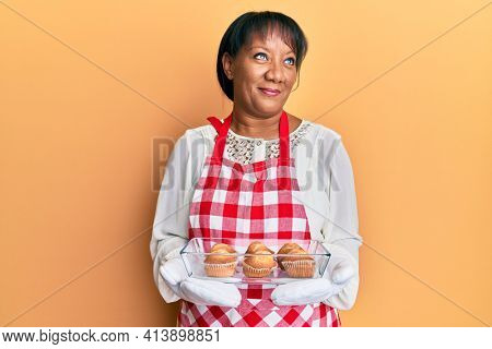 Middle age african american woman wearing baker apron holding muffins smiling looking to the side and staring away thinking.