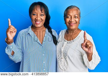 Hispanic family of mother and daughter hugging together with love surprised with an idea or question pointing finger with happy face, number one