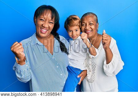 Hispanic family of grandmother, mother and son hugging together screaming proud, celebrating victory and success very excited with raised arm
