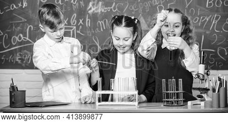School Laboratory. Girls And Boy Providing Experiment With Liquids. Test Tubes With Colorful Liquid