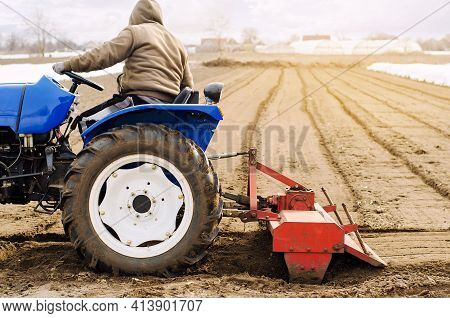 Farmer On A Tractor With Milling Machine Loosens, Grinds And Mixes Soil. Loosening The Surface, Cult