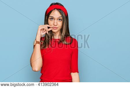 Young brunette woman wearing casual clothes mouth and lips shut as zip with fingers. secret and silent, taboo talking