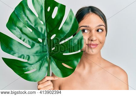 Young brunette woman holding green plant leaf close to beautiful face smiling looking to the side and staring away thinking.