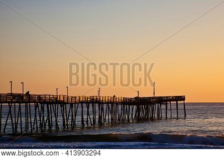 Avalon fishing Pier in the Outer Banks of North Carolina is picturesque at sunrise.  This is a popular vacation destination along the coast.