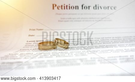 Conceptual Image For Divorce With Two Golden Wedding Ring In The Middle And Petition For Divorce As