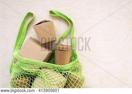 Green Mesh Tote Bag Full Of Kraft Paper Or Cardboard Eco Packages On Wooden Background.