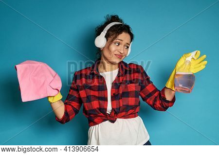 African American Woman Holding Cleaning Rag Looking At Spray With Displeasure. Concept Of House Work