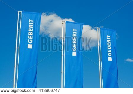 Manno, Switzerland - 18th March 2021 : View Of Three Geberit Company Flags Against Blue Sky In Switz