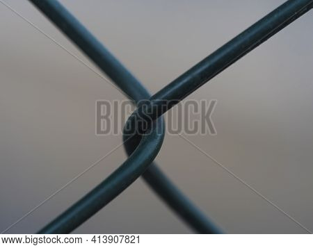 Close Up Of Green Metal Wire Fence Twist On Beige Bokeh Background. Macro Photograph Of Iron Mesh. S