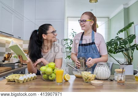Mom And Teen Daughter Cooking Apple Pie Together At Home Kitchen