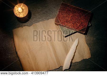 Blank Sheet Of Parchment And A Pen For Writing, Antique Books And A Burning Candle, A Desk With An A