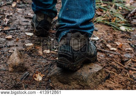 The Legs Of Tourist In Hiking Boots On A Walk In The Fall Are Walking Along A Muddy Wet Trail. Activ