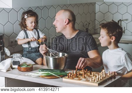 Father Whips An Omelet With A Whisk, Playing Chess With Son And Talking To Daughter. Man Doing Chore