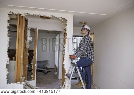 Carpenter Inspecting A Demolishing Of Interior Home During A Remodel Project.