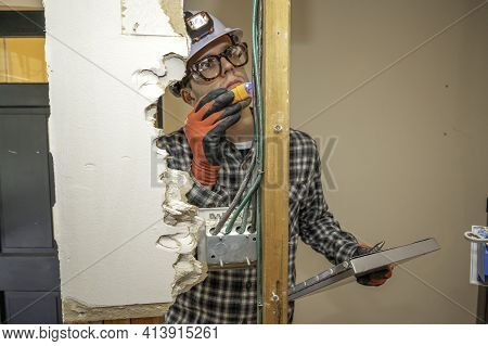 Electrician Inspecting Electrical Wiring Between Framing Studs Where The Drywall Is Removed For Home