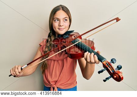 Beautiful brunette little girl playing violin smiling looking to the side and staring away thinking.