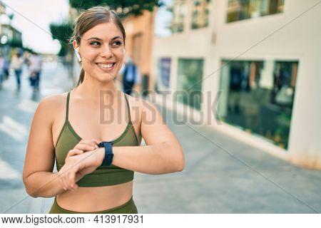 Young blonde sportswoman wearing sportswear touching watch at the city.
