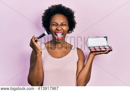 Young african american woman holding makeup brush and blush sticking tongue out happy with funny expression.