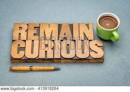 remain curious word abstract in vintage letterpress wood type with a cup of coffee, open and active mind concept