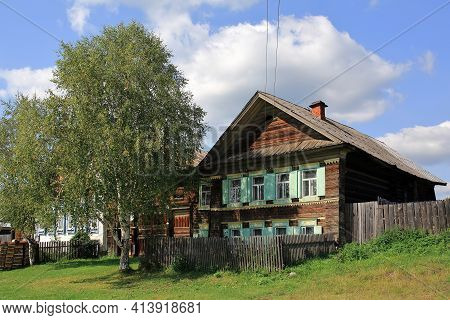 Russian Village In Summer. View Of The Old Traditional Wooden House With Carved Windows And Birch Tr
