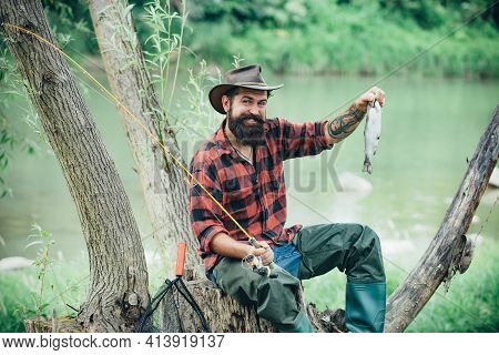Man Dressed In Shirt Fishing With Rod And Fish On The Lake. Weekend. Master Baiter. Male Hobby. Hobb