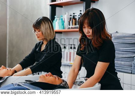 Serious Asian Female Hairdresser Wearing Uniform And Spectacles Shampooing Hair Of Young Woman Custo