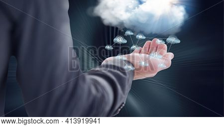 Composition of network of digital cloud icons with white cloud over hand of businessman. global technology and digital interface concept digitally generated image.
