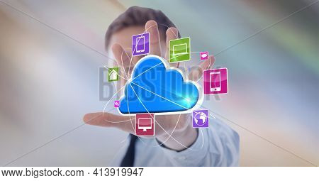 Composition of digital blue cloud with network of digital icons over hand of businessman. global technology and digital interface concept digitally generated image.