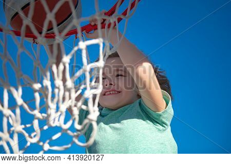 Cute Smiling Boy Plays Basketball And Making Slam Dunk. Closeup Portrait Of Kid Boy Basketball Playe