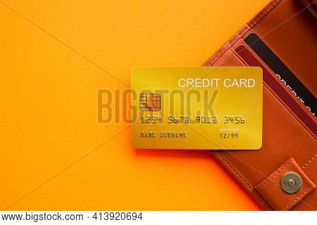 Gold Credit Card On Wellet With Orange Paper Background. For Travel Summer In Holidays. Planing Earn