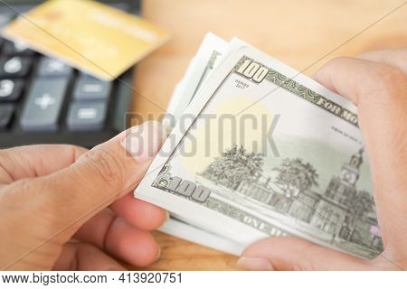 100 Dollars. Close Up Hand Woman Counting Money Bank Note With Credit Card And Calculator Blured. Pl