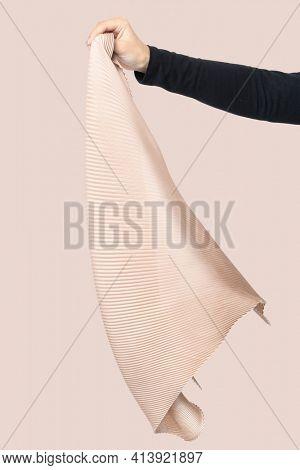 Woman's hand holding beige pleated scarf fashion studio shoot