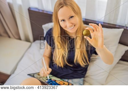 Nft Young Woman, A Digital Artist, Creates Digital Art On A Tablet At Home And Shows A Coin With The