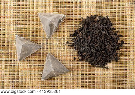 Few Tea Bags With Black Tea, Leaf Black Tea In Bamboo Spoon, Heap Of Leaf Tea On Brown Mat. Top View
