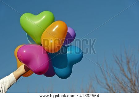 heart balloons hold by human hand isolated on blue background