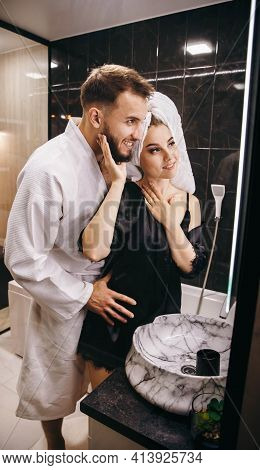 Husband And Wife In The Bathroom Fooling Around In Front Of The Mirror. Beautiful Young Couple Havin
