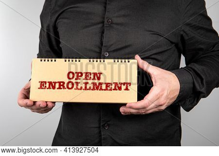Open Enrollment. Business Man With Notepad On A Light Background