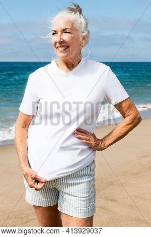 Senior woman in white tee at the beach
