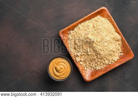 Dry Mustard Powder In A Wooden Plate And Ready-made Pasty Mustard On A Brown Background. Minimalisti