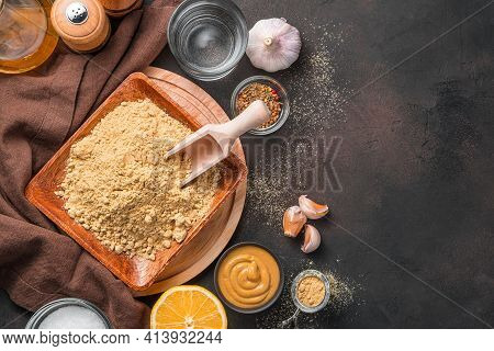 Mustard Powder, Ready-made Mustard, Spices And Lemon On A Brown Background. Top View With Copy Space