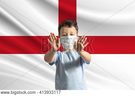 Little White Boy In A Protective Mask On The Background Of The Flag Of England. Makes A Stop Sign Wi