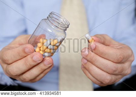 Man In Office Clothes Taking Pills, Bottle Of Medication In Capsules Close Up. Concept Of Antidepres