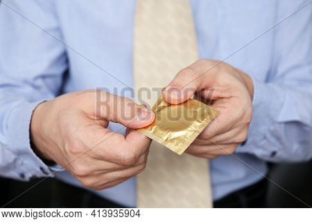 Condom In Male Hands Close Up, Safe Sex Concept. Man In Office Clothes Giving Condom In Package, Con